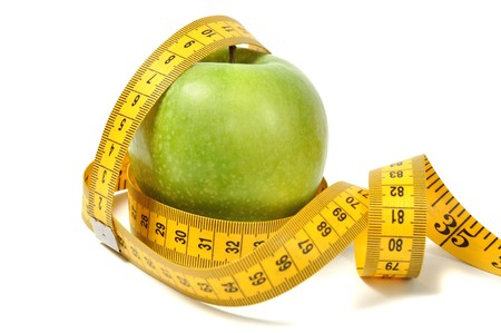 Green apple and measure tape over white