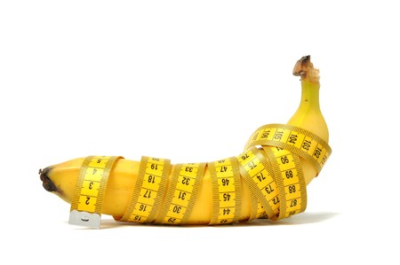 Banana and measure tape over white