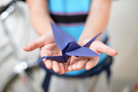 Origami crane in children hands Stock Photo
