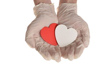 Two hearts in hand with rubber gloves isolated on white