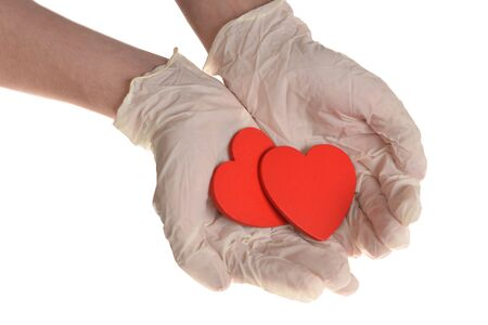 Two red hearts in hand with rubber gloves isolated on white