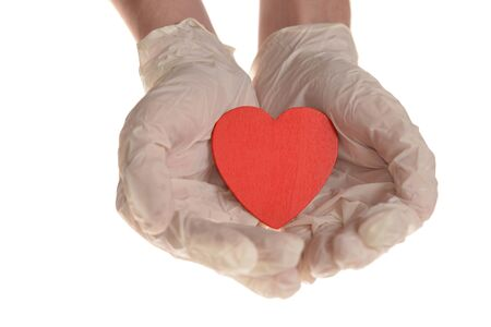 Hearts in hand with rubber gloves isolated on white