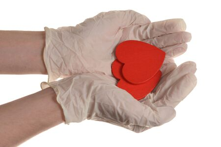 Two red hearts in hand with rubber gloves isolated on white Banco de Imagens
