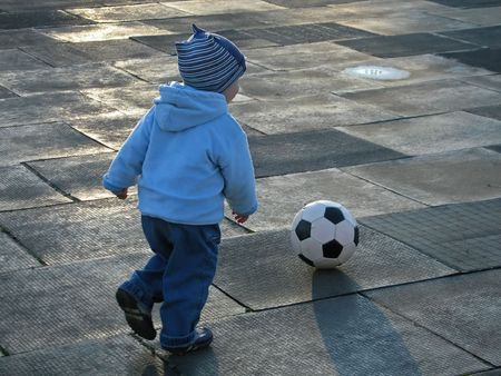 teens playing: Little child playing soccer ball
