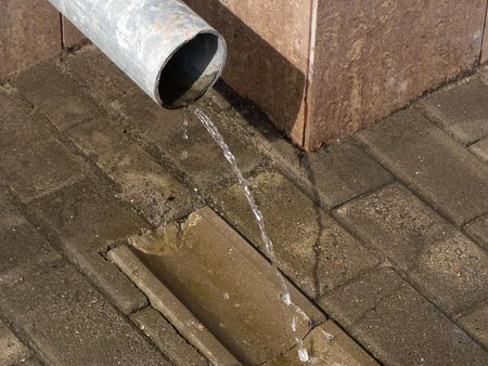 Drain pipe with flowing rain water photo