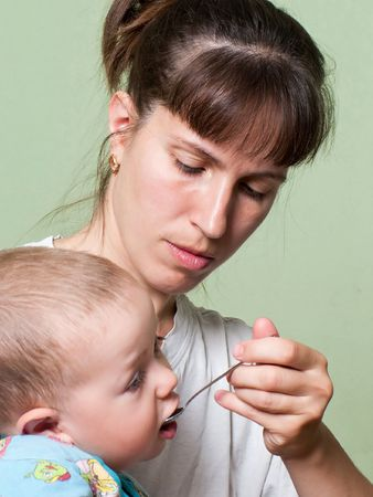 Mother and little child eating food in family care photo
