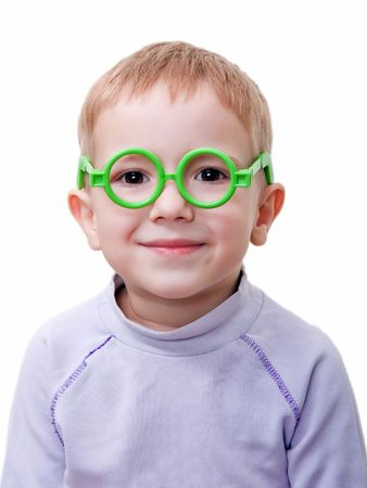 Little spectacled child smiling in green toy glass photo