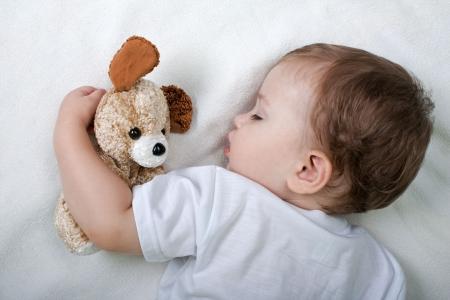 ni�o durmiendo: Peque�o ni�o durmiendo en la felicidad y el amor de familia Foto de archivo