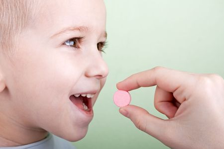 Human hand giving child medicine healthcare pill photo