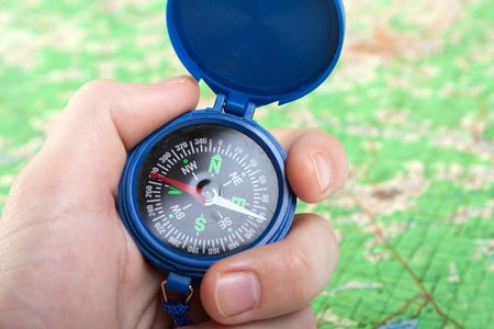 Hand holding travel north direction compass on map photo