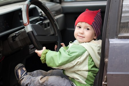 race car driver: Little smiling child boy driving sport car vehicle