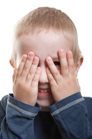 Little human child hiding hand one eye fun peeking photo