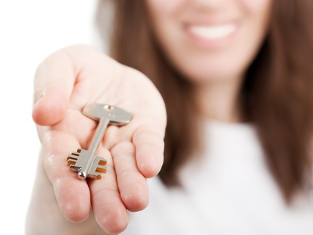 home keys: Beauty smiling female human hand holding house key Stock Photo