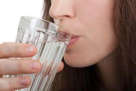 Female human hand holding liquid drink water glass photo