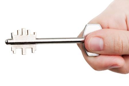abriendo puerta: Mano humana, manteniendo el bloqueo de llave de la puerta de casa de metal de acero