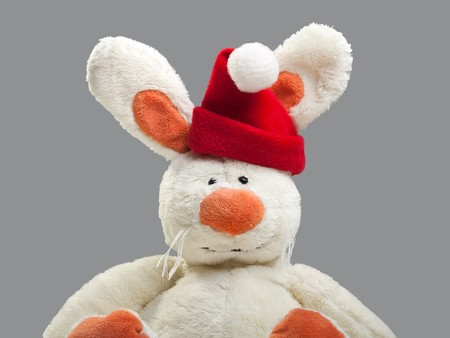 New year rabbit animal toy in red Santa Claus hat photo