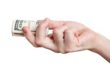Human hand holding rolled up paper dollar currency photo
