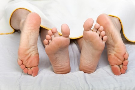 sex activity: Human sex - men and women couple naked foot on bed Stock Photo