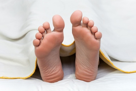 Bed blanket on dead sleeping human body foot toe photo