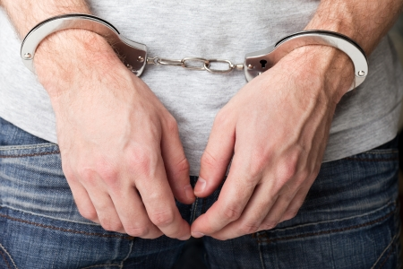 handcuffs: Police law steel handcuffs arrest crime human hand Stock Photo