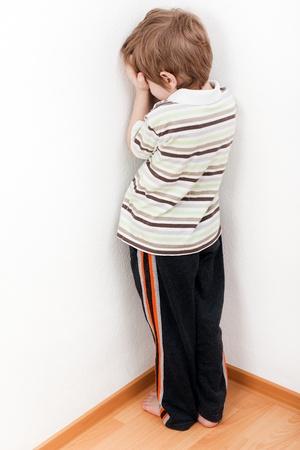 punishing: Little child boy wall corner punishment standing