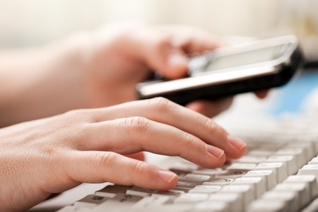 Hand holding mobile phone typing computer keyboard Stock Photo