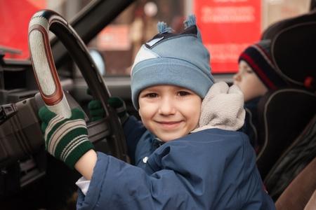 Little smiling child boy driving sport car vehicle photo