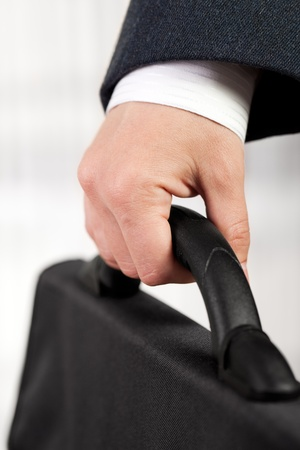 Business men in black suit hand holding briefcase photo