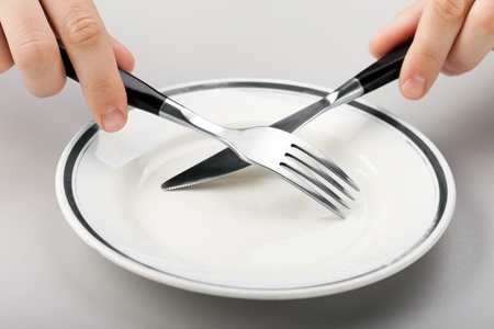 Hungry person hand holding fork knife on food plate photo