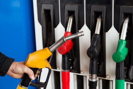 gasoline station: Mano umana, tenendo la pompa di benzina stazione gas combustibile Archivio Fotografico