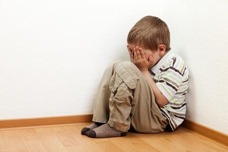 scared child: Poco pie ni�o boy pared esquina castigo Foto de archivo