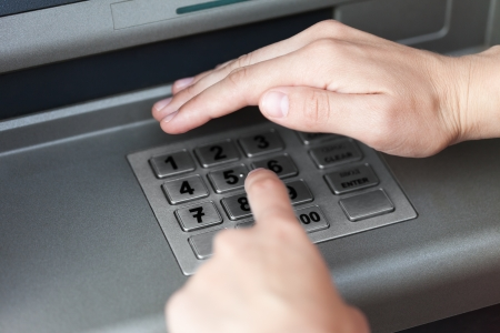 Human hand enter atm banking cash machine pin code photo