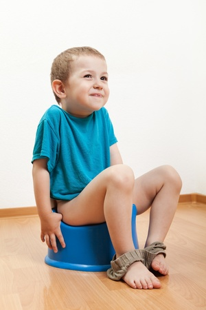 piddle: Little smiling child boy urinating toilet potty pan Stock Photo