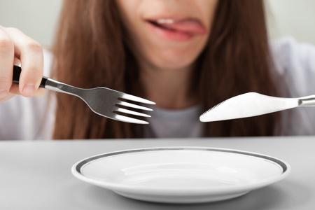fork glasses: Mano di persona affamata tenendo coltello forchetta sul piatto di cibo