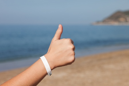 Summer vacations - woman hand gesturing thumb up success sign on sea sand beach Stock Photo - 10826237