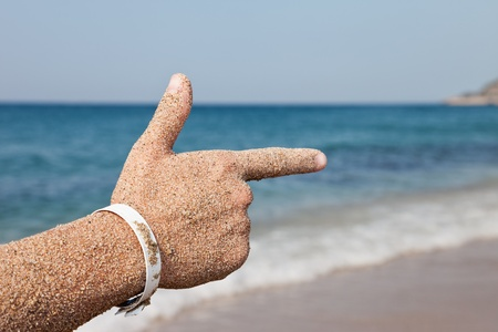 forefinger: Summer vacations - woman hand index finger pointing direction to sea sand beach