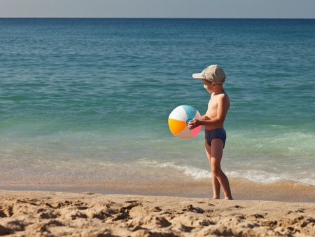 Summer vacations - little child boy hand holding inflatable ball toy on sea sand beach photo