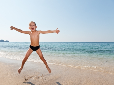 Summer vacations - little smiling child boy jumping on sea sand beach
