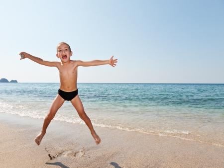 ni�o saltando: Vacaciones de verano - poco ni�o sonriente ni�o saltando en la arena, mar y playa