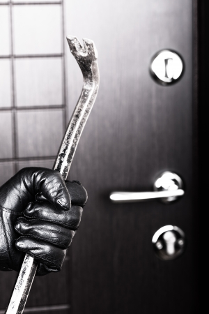 burglar protection: Crime scene - criminal thief or burglar hand in gloves holding metal crowbar break opening home door lock