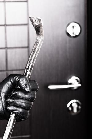 Tatort - Straftaten Dieb oder Einbrecher Hand in Handschuhen halten Metall Brecheisen brechen Eröffnung Hause Türschloss Lizenzfreie Bilder