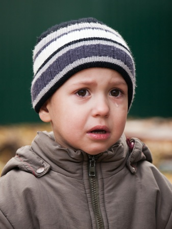 Kleines Kind weinen mit Tränengas auf Gesicht
