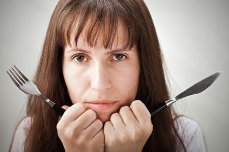 Hongerige vrouw hand holding vork en mes Stockfoto