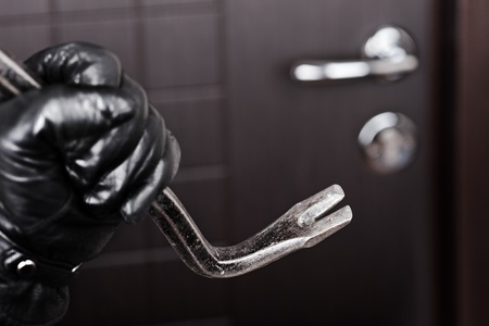 Crime scene - criminal thief or burglar hand in gloves holding metal crowbar break opening home door lock