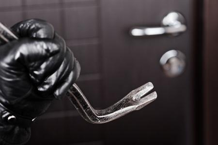 Crime scene - criminele dief of inbreker hand in handschoenen die metalen koevoet breken opening thuis deurslot