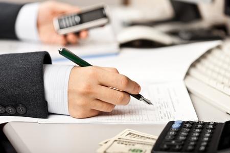 Arbeiten Geschäftsmann Hand Stift schriftlich Papierdokument bei Büroarbeitsplatz Lizenzfreie Bilder