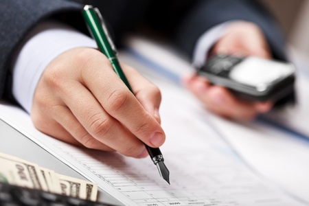 Working business man hand pen writing paper document at office workplace photo