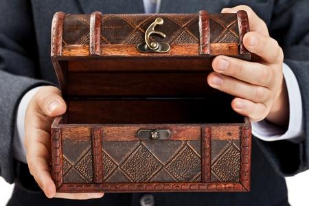 Zakenman hand die oude antieke bruine houten schatkist of doos witte geïsoleerde