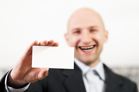 Smiling bald man hand holding blank white business card photo
