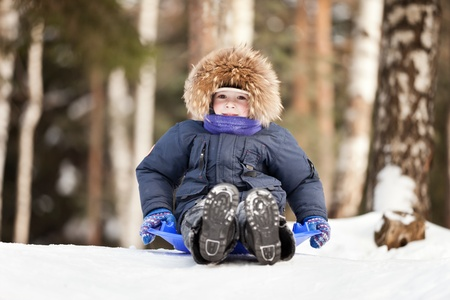 Little smiling child boy sled tobogganing on winter snow hill Stockfoto